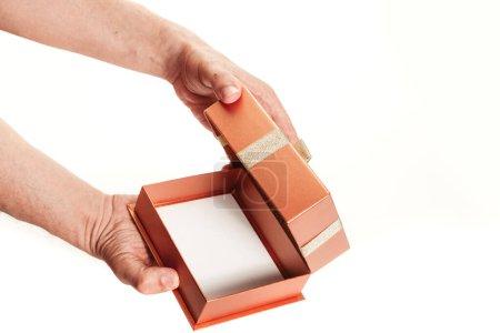 Photo pour Nous choisissons l'emballage pour un cadeau. Les mains ont ouvert une boîte vide avec une boucle sur le couvercle et un fond blanc en gros plan - image libre de droit