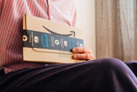 Man unboxing box with Amazon logotype
