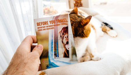 Man preparing to travel with cat reading brochure from Switzerla