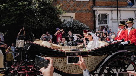 Photo for WINDSOR, ENGLAND - MAY 19 2018: Prince Harry, Duke of Sussex and Meghan, Duchess of Sussex leave Windsor Castle in Ascot Landau carriage during a procession after getting married at St Georges Chapel - Royalty Free Image