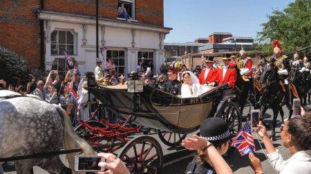 Foto de Windsor, Inglaterra - 19 de mayo de 2018: Príncipe Harry, duque de Sussex y Meghan, licencia de Duquesa de Sussex el castillo de Windsor en transporte Ascot Landau durante una procesión después de casarse en St Georges Chapel - Imagen libre de derechos