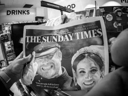 LONDON, ENGLAND - MAY 20, 2018: POV The Sunday Times front cover newspaper in British press kiosk featuring portraits of Prince Harry and Meghan Markle black and white ifestyle event