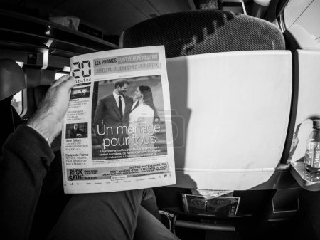 Photo for FRANCE - MAY 20, 2018: Man reading in first class of a TGV SNCF train the cover newspaper of 20 minutes featuring portraits of Prince Harry and Meghan Markle lifestyle event - Royalty Free Image