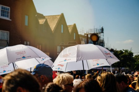 Photo for WINDSOR, UNITED KINGDOM - MAY 19, 2018: People protecting from sun with Marks and Spencer umbrellas that has changed the name to Markle and Sparkle in honour of the Royal Wedding - Royalty Free Image