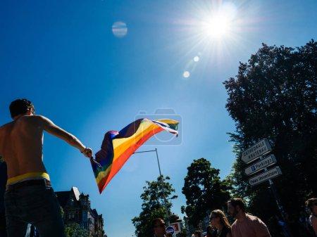 Gay pride waving LGBT rainbow flag