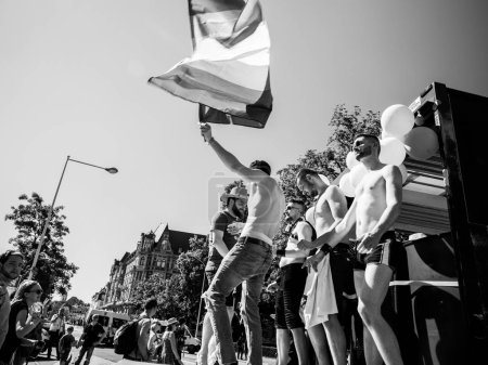 Group of boys waving gay pride flag - black and white