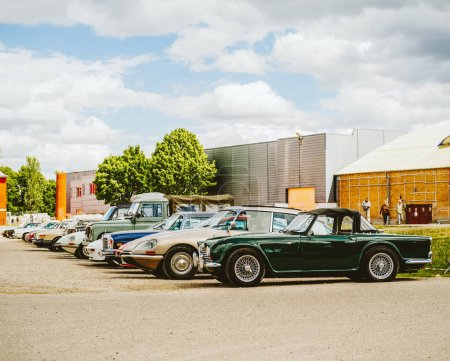 STRASBOURG, FRANCE - APR 30, 2018: Multiple old vintage cars parked on a French street including BMW, Porches, Triumph, Citroen  all arranged in a row on a spring day