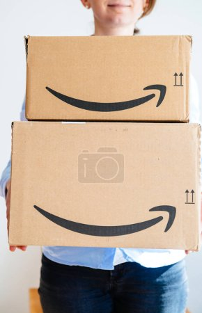 Woman holding multiple Amazopn boxes with logotype