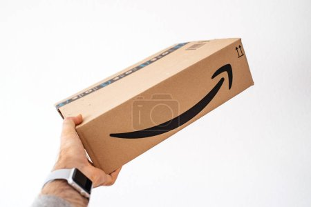 Man holding Amazon Prime cardboard delivery box