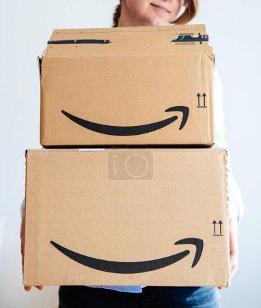 Smiling Woman holding multiple Amazopn boxes with logotype