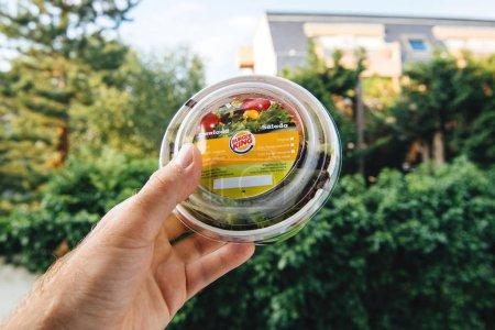 PARIS, FRANCE - JUNE 5, 2018: Burger King fresh salad with Burger King logotype in man hand against green outdoor background - square image organic salad bio