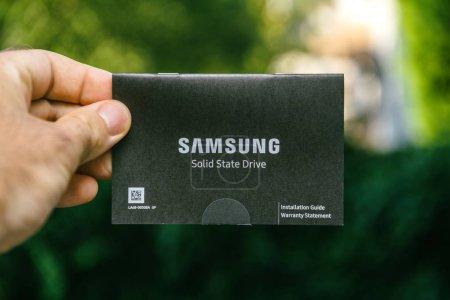 Foto de París, Francia - 03 de agosto de 2018: Hombre mano instruciton empaquetado de Nvme Pcie Ssd disco de disco duro con alta velocidad de lectura y escritura 870 Samsung Pro - Imagen libre de derechos