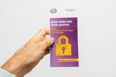 PARIS, FRANCE - AUG 1, 2018: Man holding against white background a leaflet containing a fidelity discount card from Deutschland Card From Esso fuel station