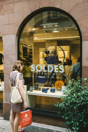 STRASBOURG, FRANCE - JUL 22, 2017: Elegant French woman admiring the leather products in fashion store Le tanneur with big SALES Soldes stickers on window showcase