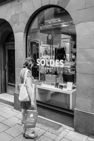 STRASBOURG, FRANCE - JUL 22, 2017: Elegant French woman admiring the leather products in fashion store Le tanneur with big SALES Soldes stickers on window showcase - black and white
