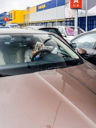 Photo pour Delft, Pays-Bas - 23 août 2018: Vue de la rue de l'élégante femme lisant Ikea meubles catalogue magazine à l'intérieur de la voiture garée sur le parking d'Ikea dans le magasin principal dans les pays-bas, le siège social d'Ikea - image libre de droit