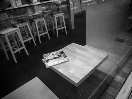 DELFT, NETHERLANDS - AUG 23, 2018: Ikea furniture catalogue magazine on the table made by IKEA - view from the street through glass inside store - black and white