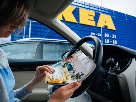 Photo pour Delft, Pays-Bas - 23 août 2018: Femme élégante catalogue magazine de meubles Ikea à l'intérieur de la voiture garée sur l'échelle de lecture Ikea de stationnement dans le magasin principal dans les pays-bas, siège social de Global Ikea - image libre de droit