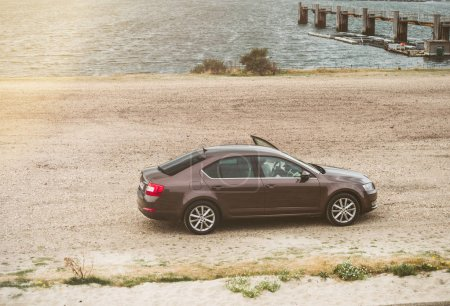 Vrouwenpolder, Netherlands - Aug 25, 2018: Luxury Skoda car parked in the bay - elevated view - rainy cloudy netherlands weather with driver open door