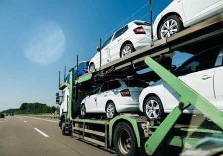 Photo pour Vue de la remorque longue camion blanc générique transportant des voitures neuves et circulant sur l'autoroute au soleil sous le ciel bleu - image libre de droit