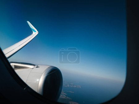 Plane window view above coast