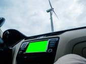 Car dashboard GPS display and large wind power windmill green cr