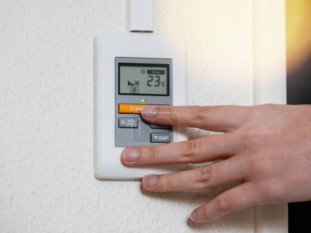 Woman choosing temperature Air Conditioning system modern