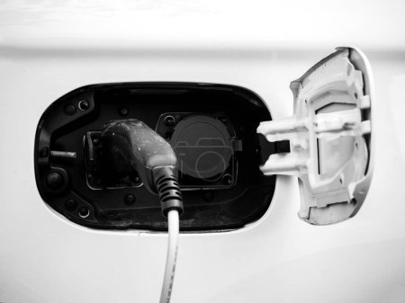Energy power cable of electric car charger being plugged in at the modern refueling center station