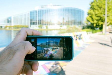 Foto de Estrasburgo, Francia - 12 de Sep, 2018: Foto de toma de hombre con iphone smartphone teléfono con cartel de cartel de Saveyourinternet frente a la fachada sur del Parlamento Europeo - Imagen libre de derechos