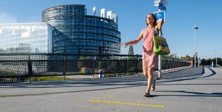 Foto de Estrasburgo, Francia - 12 de Sep, 2018: Mujer que camina delante de la gran protesta bandera Save su Internet con Parlamento Europeo en el fondo temprano en la mañana - Imagen libre de derechos