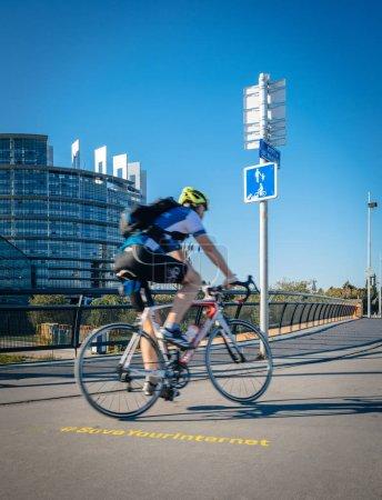Foto de Estrasburgo, Francia - 12 de Sep, 2018: Ciclista Senior y gran protesta bandera Save Your Internet sobre asfalto con Parlamento Europeo en el fondo temprano en la mañana - Imagen libre de derechos