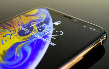 PARIS, FRANCE - SEP 25, 2018: Detail of the new iPhone Xs and Xs Max smartphone model by Apple Computers close up of golden Apple iPhone mobile phone device on reflective yellow technology background
