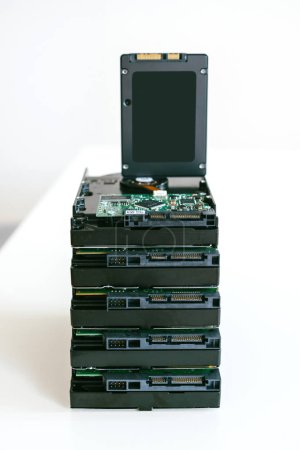 Stack of multiple HDD hard disk drives with modern fast SATA SSD solid state drive placed vertically above them