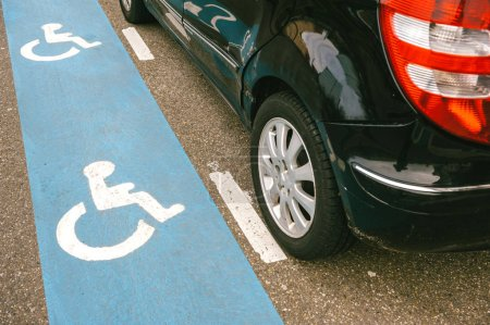Black car parked on the disabled blue sign during the day
