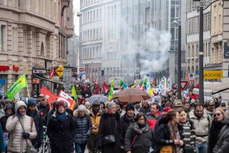 Foto de Estrasburgo, Francia - 22 de marzo de 2018: Granada de humo en fondo de la multitud como General de la Cgt Confederación de trabajadores laborales con cartel en demostración de protesta contra cadena de gobierno francés Macron de - Imagen libre de derechos