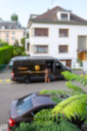 Photo for PARIS, FRANCE - AUG 24, 2017: Defocused blur view of Courier enters UPS United PArcel Service brown delivery van with cardboard parcel in the hands delivering the on time delivering package parcel - Royalty Free Image