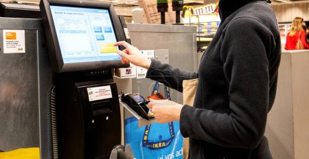 Woman using digital touchscreen to pay for products