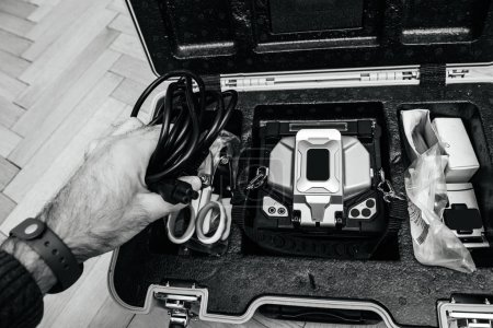 Photo for Technician preparing to use the modern innovative and powerful performance active clad-alignment splicer used for splicing an array of thin optical fiber types - holding power cable - Royalty Free Image