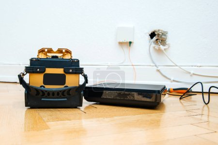 Photo for Modern FTTH fiber installation at home with new arc clad-alignment fusion splicer used for splicing an array of thin optical fiber types with CATV on wall socket and tv internet receiver tuner - Royalty Free Image