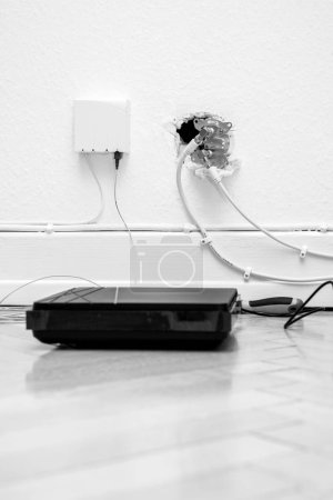 Photo for Fiber optic installation at home with obsolete CATV and new FTTH fiber outlets and internet receiver on parquet floor - Royalty Free Image