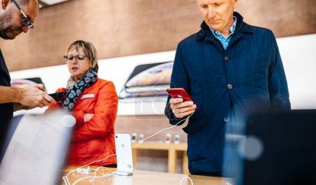 Foto de París, Francia - 26 de octubre de 2018: Apple Store con cliente senior masculino y femenino admirando el nuevo iphone más reciente teléfono smartphone de Xr - elegir imagen vertical de color rojo - Imagen libre de derechos