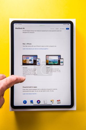 Photo for PARIS, FRANCE - NOV 14, 2018: Man hand holding unboxing unpacking of new iPad Pro by Apple Computers tablet in office with yellow background - featuring Liquid Retina Apple website with MacBook Air - Royalty Free Image