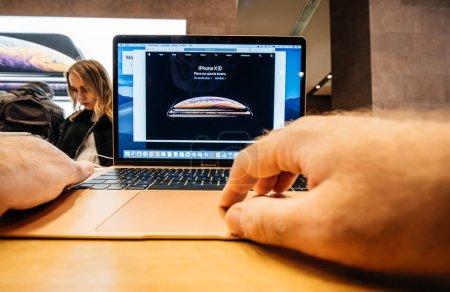 Photo pour Paris, France - 8 novembre 2018: Main de l'homme toucher le nouveau Apple Macbook Air mince ordinateur portatif avec écran Retina et nouveau processeur - lecture site Web avec l'iphone Xs - image libre de droit