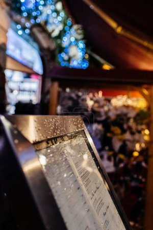 Photo pour Menu restaurant couvert de gouttes d'eau et de neige au centre du marché de Noël en ville européenne - image libre de droit