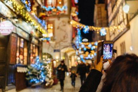 Foto de Vista de las personas que toman fotografías en smartphone teléfono móvil dispositivos de las guirnaldas y decoraciones iluminan la calle de Estrasburgo posterior - posterior vista la visita del mercado de Navidad - Imagen libre de derechos