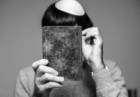 Photo for Jewish male wearing Kippah praying mahzor prayer book from 1920 used on the High Holy Days of Rosh Hashanah and Yom Kippur - black and whtie - Royalty Free Image