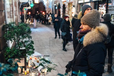 Photo for STRASBOURG, FRANCE - DEC 13, 2018: Sad people mourners gathered on Rue des Orfevres to attend a vigil with multiple light candles flowers and messages for the victims of terrorist Cherif Chekatt at - Royalty Free Image