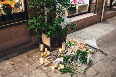 Photo for STRASBOURG, FRANCE - DEC 13, 2018: Flowers and messages on Rue des Orfevres vigil with multiple light candles flowers and messages for the victims of terrorist Cherif Chekatt at Christmas Market - Royalty Free Image