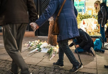 Photo for STRASBOURG, FRANCE - DEC 13, 2018: Senior couple holding hands walking near mourning place on Rue des Orfevres to attend a vigil with multiple light candles flowers and messages for the victims of - Royalty Free Image