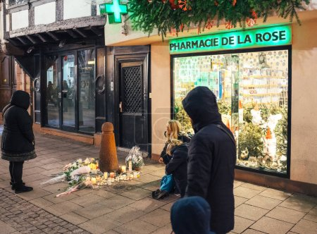 Photo for STRASBOURG, FRANCE - DEC 13, 2018: Young girls lighting candles on Rue des Orfevres to attend a vigil with multiple light candles flowers and messages for the victims of terrorist Cherif Chekatt at - Royalty Free Image